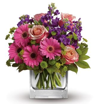 Sweet Promises. Description: Like the dawn of a fine spring day, this pretty pink gift of gerberas, roses and delicate blue delphinium promises happiness!