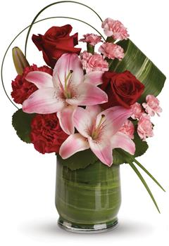Delicate Dance. Description: This gorgeous arrangement delivers the spirit of adventure. It is a unique mix of red roses, pink lilies, leaves and lily grass arranged in a chic leaf lined vase.