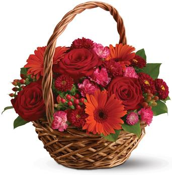 Warm Wishes. Description: Rich red roses, pretty pink carnations and sunny orange gerberas make this basket a glorious, go-anywhere garden.