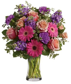 Pure Bliss. Description: Give the gift of pure bliss! Lush, lavish and luxurious, this beautiful bouquet of roses, gerberas, stock and carnations in a vase is an instant mood enhancer.