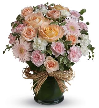 She is Lovely. Description: Indeed she is! Show her with this soft symphony of feminine blooms, including roses, gerberas and carnations in a raffia lined vase.