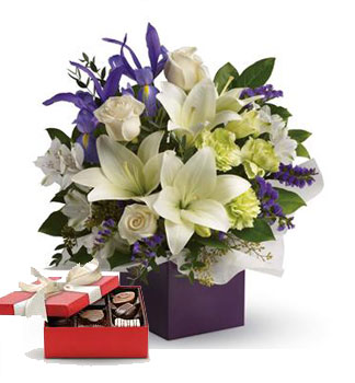 Graceful Beauty. Description: Gorgeous white lilies and delicate blue iris dance gracefully with roses and alstroemeria in this luxurious arrangement.