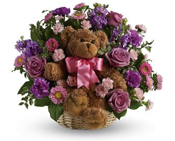 Cuddles for Her. Description: Welcome the new bundle of joy to the family with this basket arrangement of lavender and pink blooms and a delightful bear.