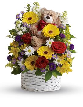 Worldly Welcome. Description: Send this mixed arrangement of sweet white and yellow daisies, red roses, stock and adorable bear. Arriving with it, it is sure to bring lots of smiles.