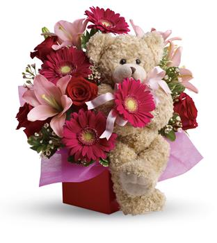 Stylish Celebration. Description: Send a smile and a hug with this stylish mixed arrangement of hot pinks and reds accented with a snuggly bear that everyone will want to hold. Simply charming!