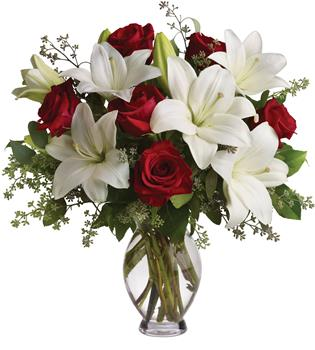 Hooray for Love. Description: Put these words into flowers with this magnificent arrangement of red roses and white lilies accented with fresh greenery delivered in a classic clear glass vase.