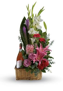 Blushing Celebration. Description: Go all out for your special someone with this opulently awesome array of lavish flowers and sparkling wine, hand arranged in a wicker basket. It is an absolutely irresistible gift.