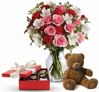 It Looks Like Love. Description: Send this beautiful gift set including a delicious box of chocolates and delightful bear paired with a vase arrangement of light red and pink blooms.