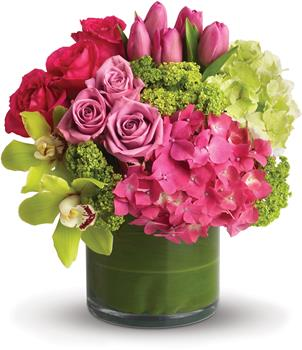Floral Fantasy. Description: Upscale and uptown. This fantastic arrangement is a beauty and a half to behold. Overflowing with gorgeous blossoms and delivered in a leaf-lined cylinder vase, it is truly a floral fantasy.