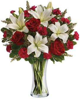 Infinite Love. Description: Timeless romantic red roses and fragrant white lilies in a classic glass vase - a sweet yet spectacular way to express what is in your heart.
