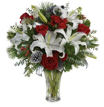 Christmas Delight. Description: Take your gift-giving to new heights with this dramatic arrangement! Classic red roses, snowy lilies and naturally festive berries are presented in a complementing vase.