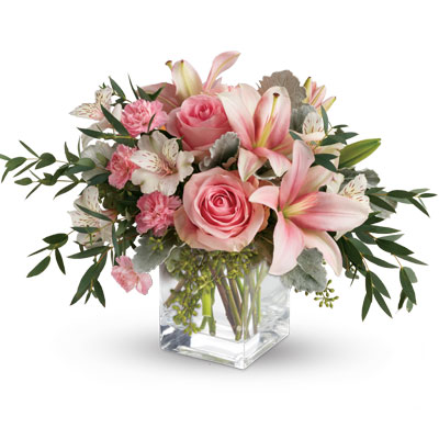 Pink Flora. Description: Just fabulous! From its perky vase and perfect pink roses, to its textural greens and dramatic pink lilies, this chic bouquet is flora at its finest!
